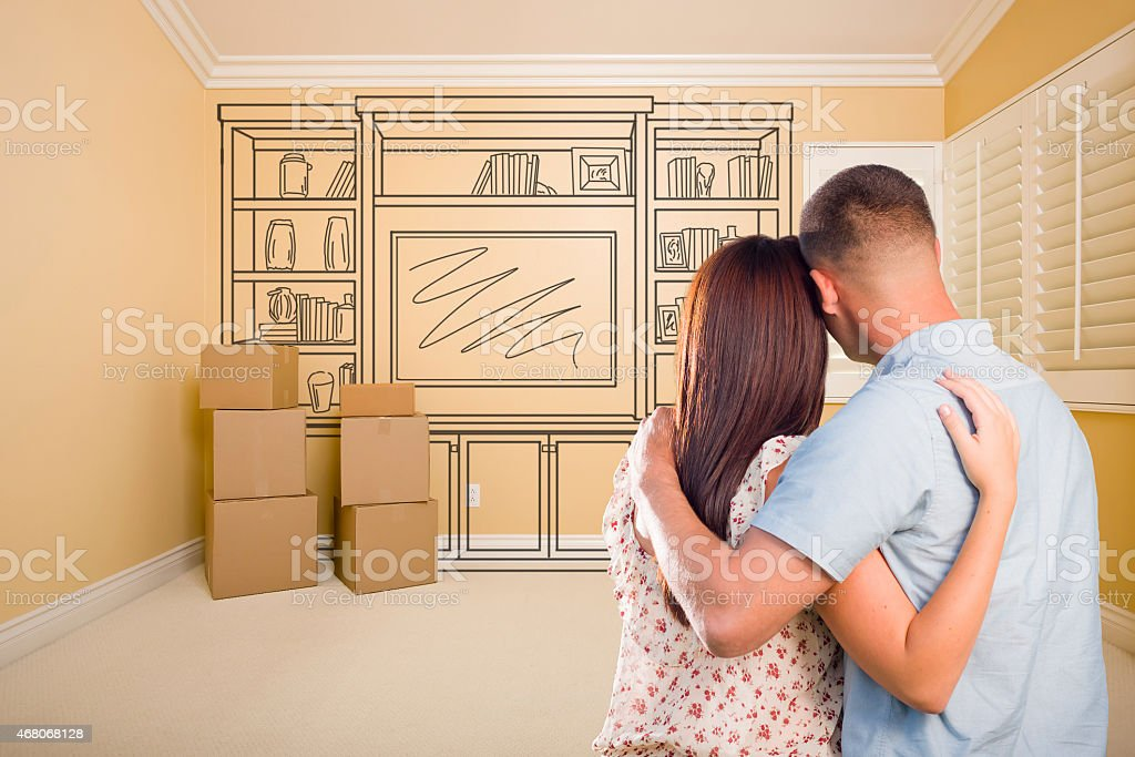 Military Couple In Empty Room with Shelf Drawing on Wall stock photo
