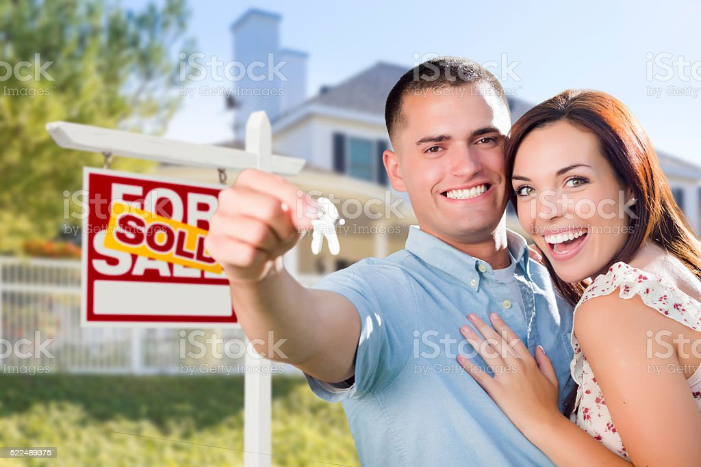 Military Couple In Front of Home, House Keys and Sign stock photo