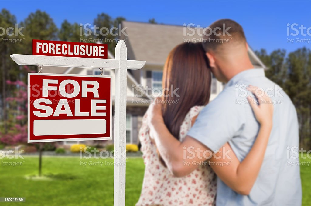 Military Couple Standing in Front of Foreclosure Sign and House stock photo