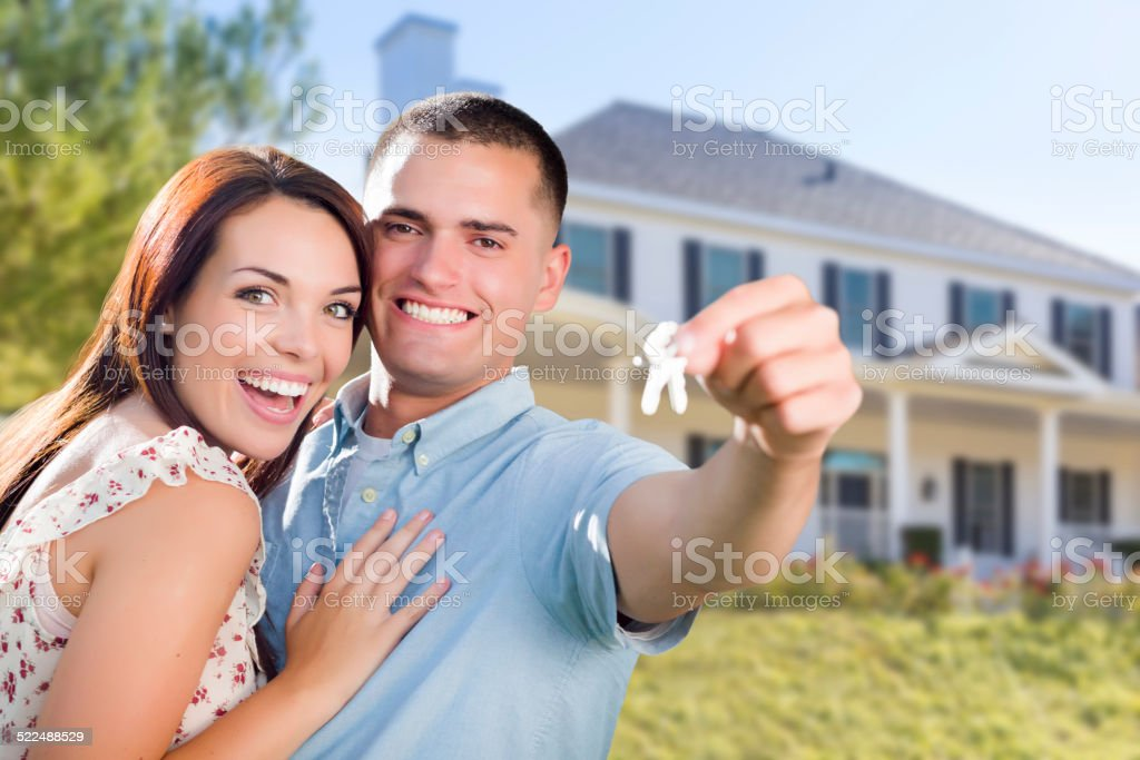 Military Couple with House Keys In Front of New Home stock photo