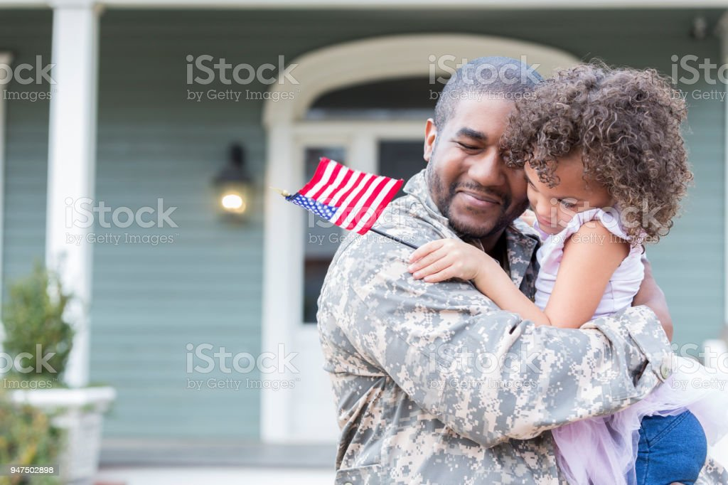 Military dad hugs preschool age daughter stock photo