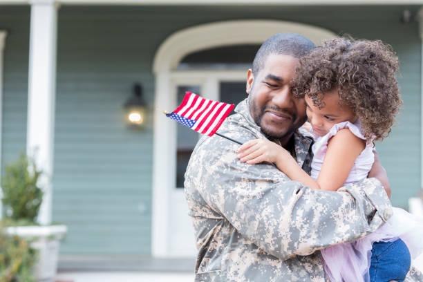 Military dad hugs preschool age daughter stock photo