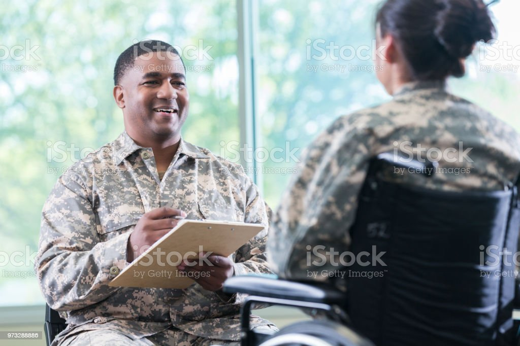 Military doctor talks with patient in wheelchair Military doctor or mental health professional talks with a female soldier in a wheelchair. The doctor is asking her questions. He is holding a clipboard. Adult Stock Photo