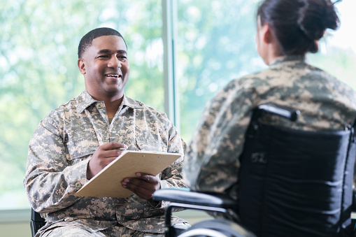 Military Doctor Talks With Patient In Wheelchair Stock Photo - Download Image Now