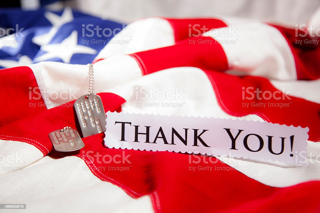 Military dog tags beside 'Thank You' note. American flags. Patriotism. stock photo