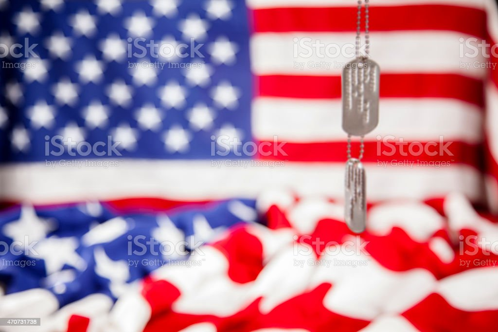 Military dog tags hang in front of American flags. Patriotism. stock photo