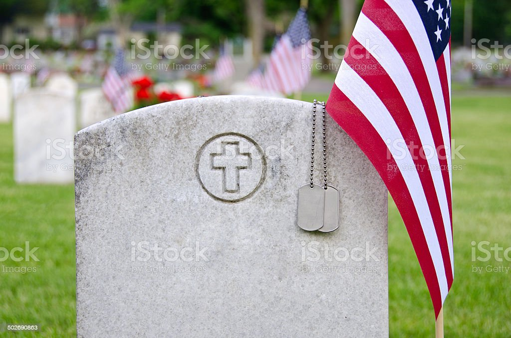 Military dog tags and American flag on a veteran\'s tombstone.
