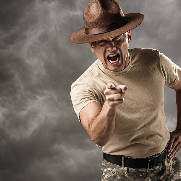 Military Drill Sergeant Barking Orders A mature caucasian male drill sergeant in military uniform points at the viewer and yells commands. sergeant stock pictures, royalty-free photos & images