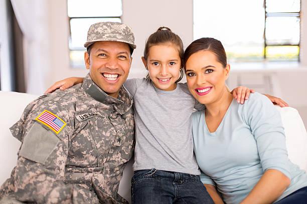 militär familie sitzen auf dem sofa - camouflagekleidung mädchen stock-fotos und bilder