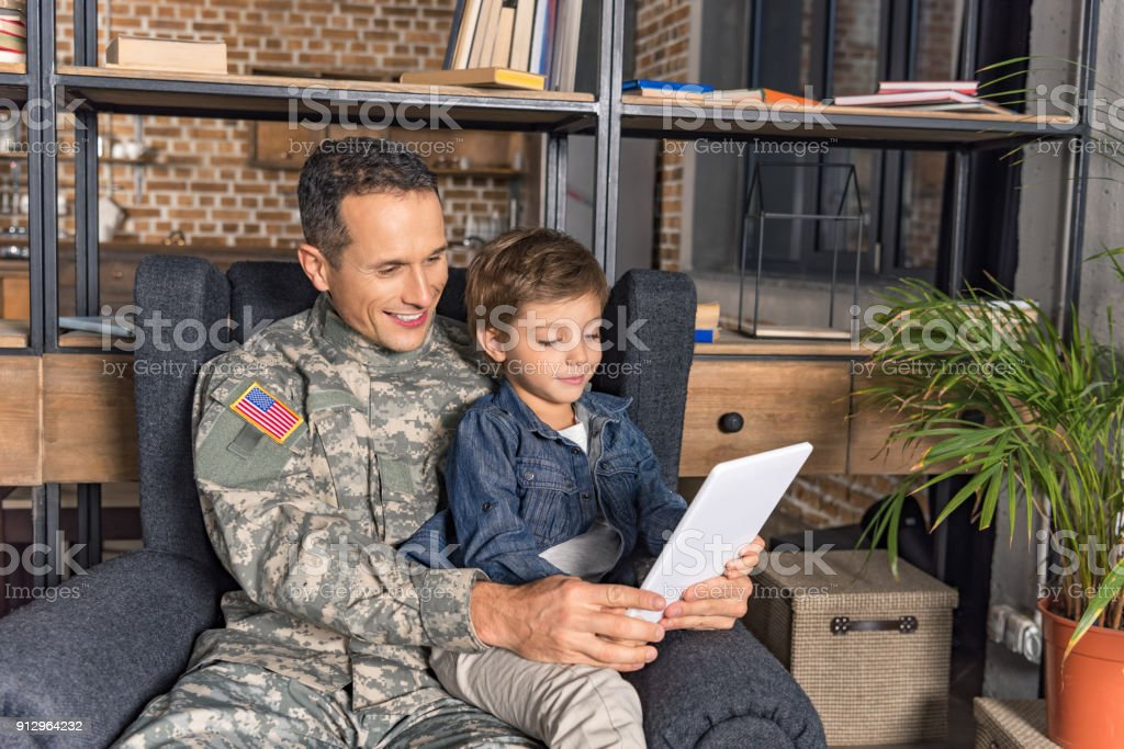 military father and son using tablet stock photo