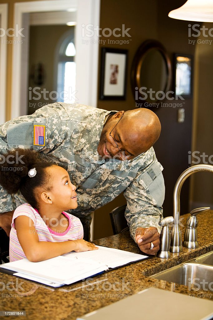 Military father helping daughter with homework  stock photo