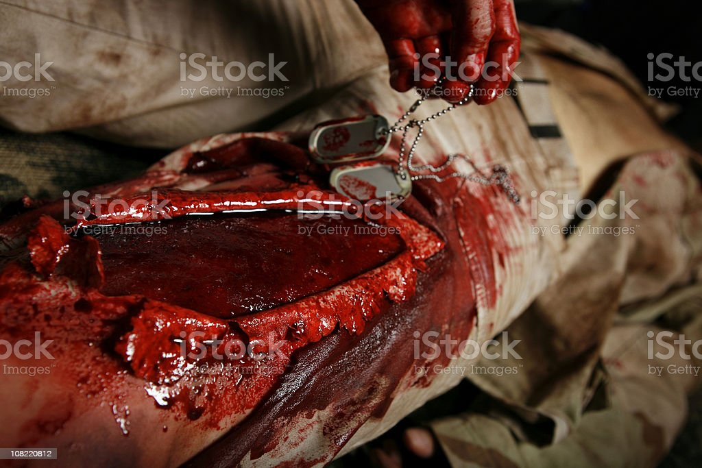 Military Field Medic Recovering Dog Tags From Fallen Soldier royalty-free stock photo