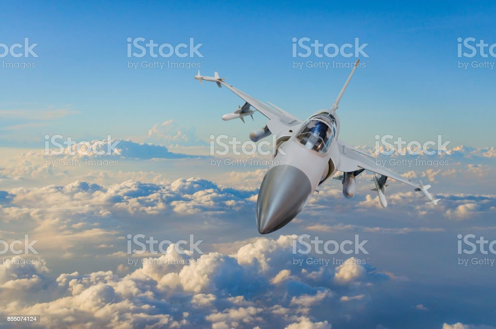 Military fighter jet against a blue sky with a backlight from below. stock photo