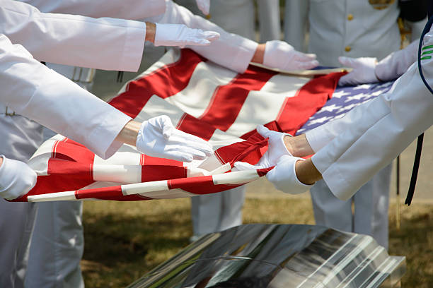 Military Funeral American Flag being Folded over Casket stock photo