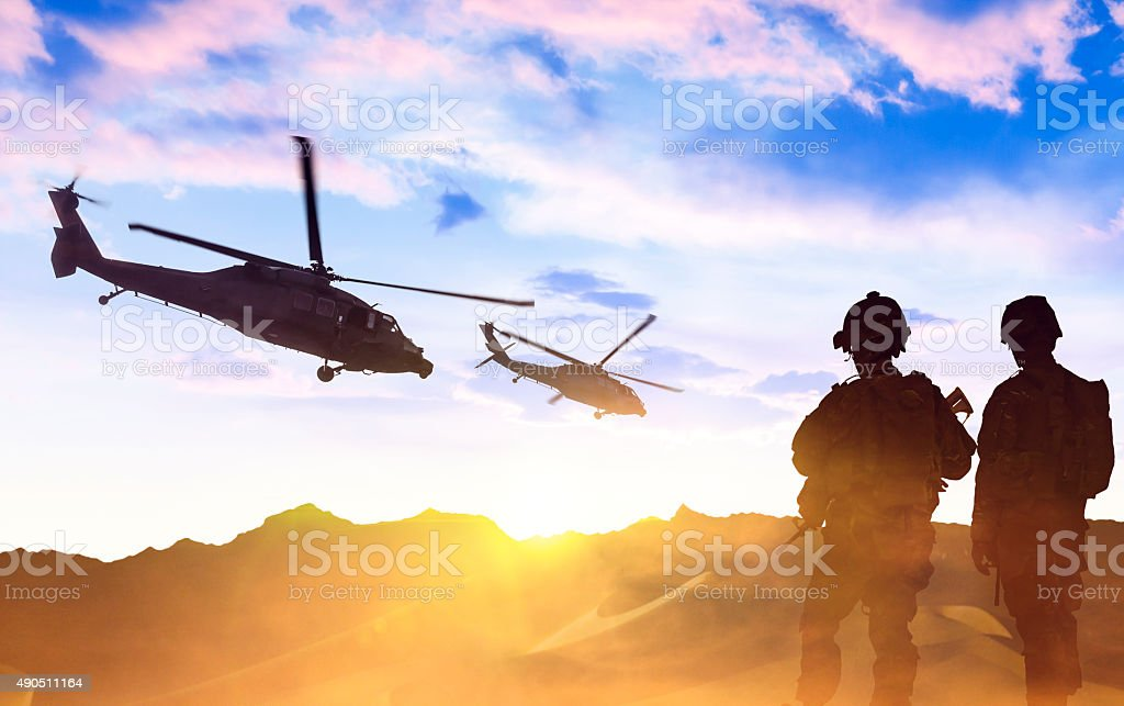 Military Helicopter and Army Soldiers at sunset stock photo