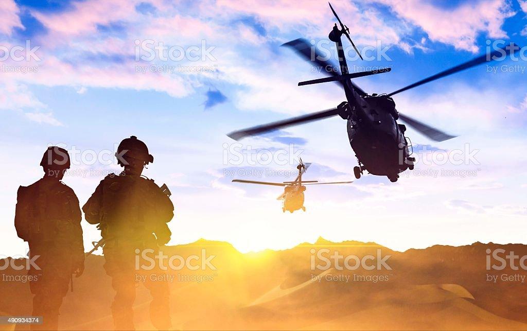Helicóptero Militar e Exército dos Soldados no pôr-do-sol - foto de acervo