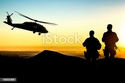istock Military Helicopter and Army Soldiers Overlook the Setting Sun 156300681