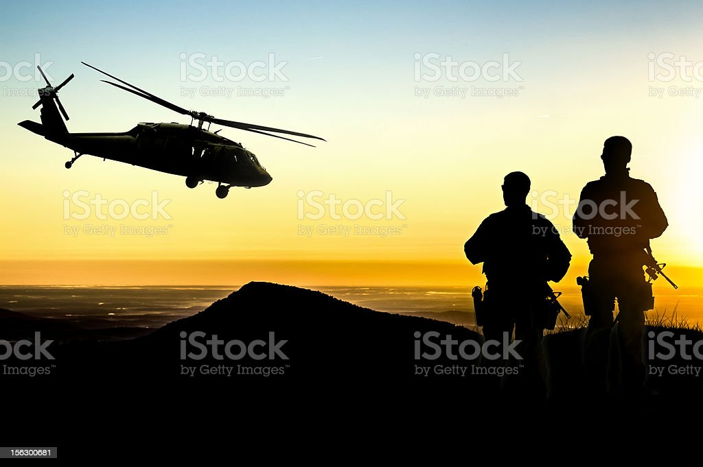 Military Helicopter and Army Soldiers Overlook the Setting Sun stock photo