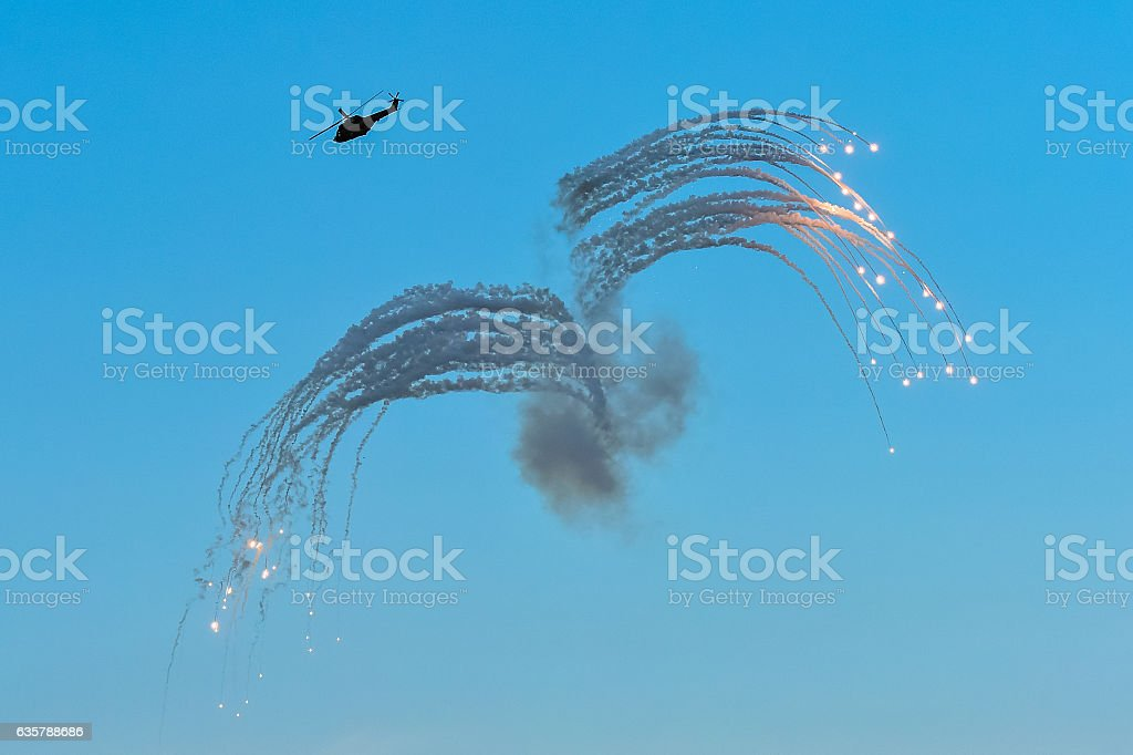 Military helicopter in action, launching rockets flares at an Ai stock photo