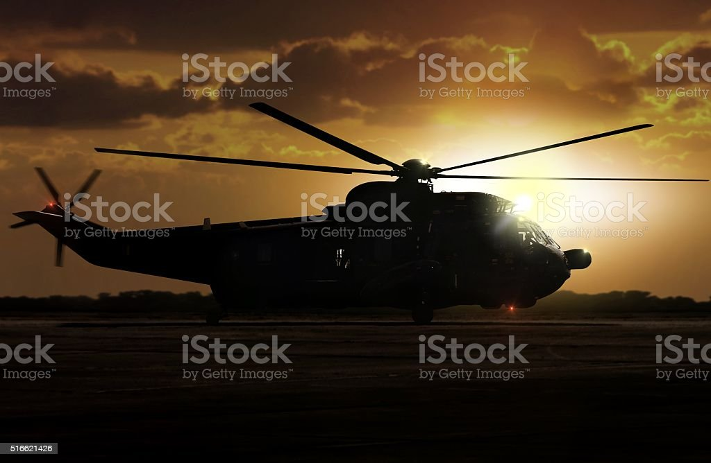 Military helicopter on airfield during sunset stock photo