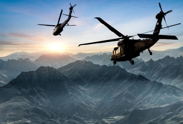Military Helicopters flying against sunset stock photo