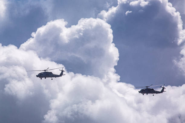 Military Helicopters flying through Storm Clouds stock photo