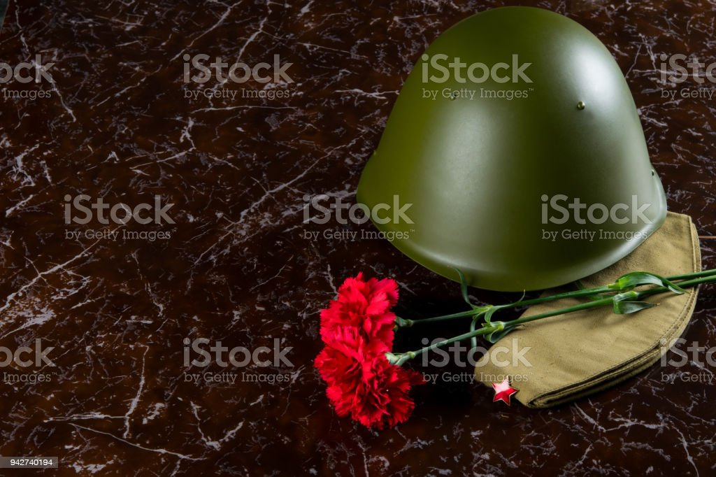 military helmet, carnations and a pilot's cap, against the background of the monument stock photo