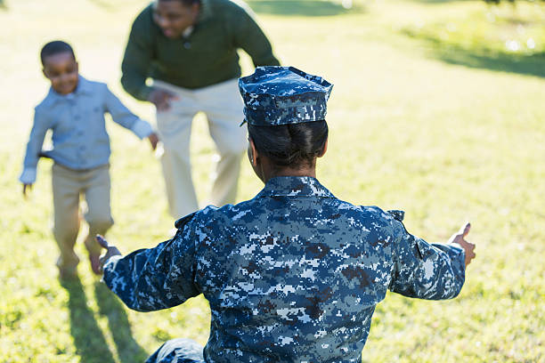 Military homecoming, navy mother reaching for son stock photo