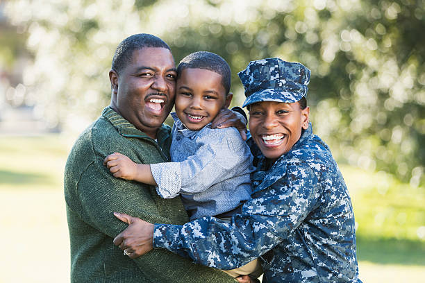 Military homecoming, navy servicewoman with family stock photo