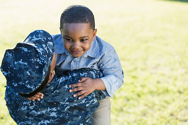 Military homecoming, navy servicewoman with little boy stock photo
