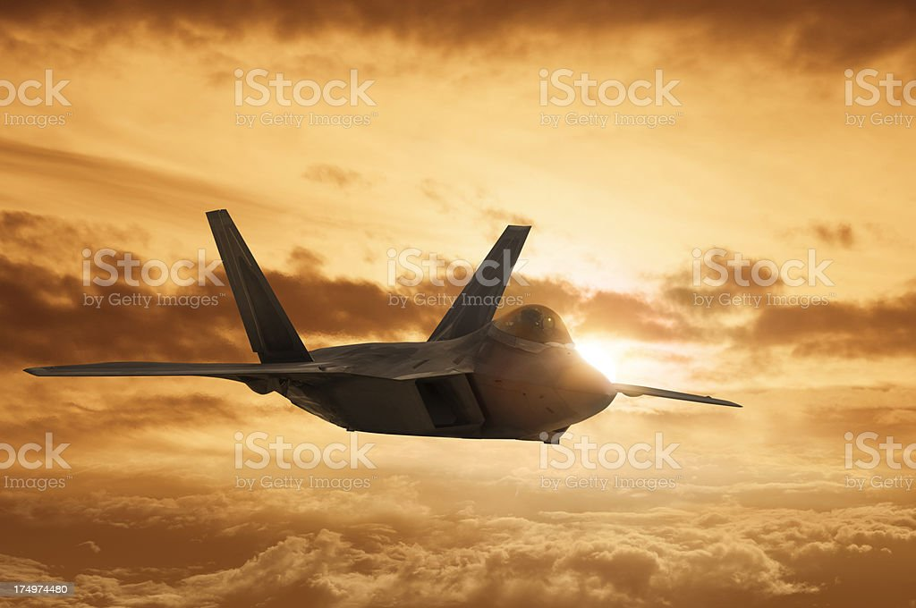 F22 Military Jet soars across a Dramatic Sunset stock photo