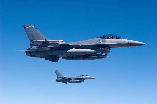 Military Jets in Flight Two F-16's in formation. air force stock pictures, royalty-free photos & images