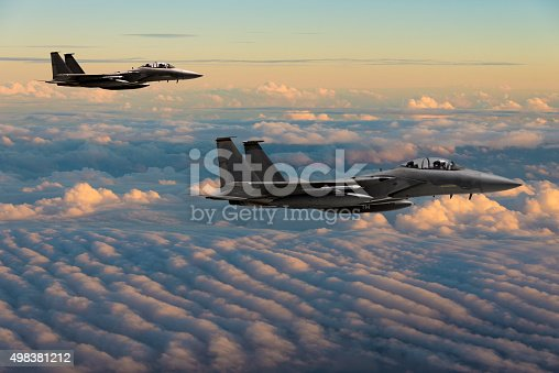 F-15 Eagle fighter jets flying above clouds
