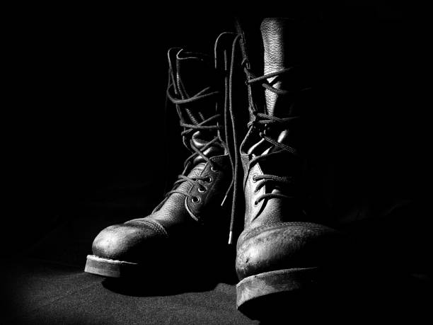 Military leather boots over black background stock photo