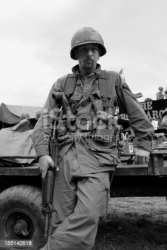 US Air Cavalry soldier  from the Vietnam war era stands next to a military vehicle.Picture has been aged to give the feel of a vintage photograph.