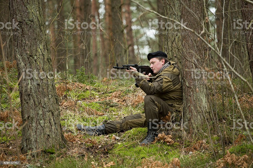 a military man in the woods with a Kalashnikov assault rifle, autumn...