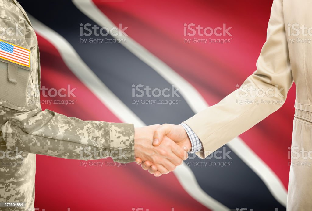 USA military man in uniform and civil man in suit shaking hands with national flag on background - Trinidad and Tobago stock photo