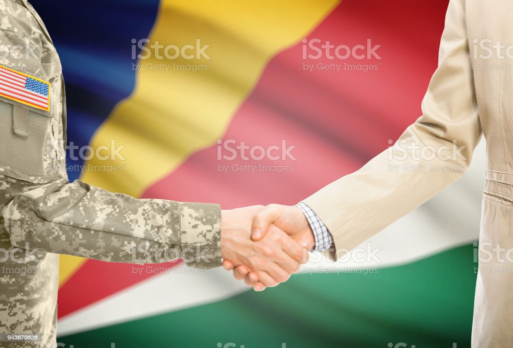 USA military man in uniform and civil man in suit shaking hands with adequate national flag on background - Seychelles stock photo
