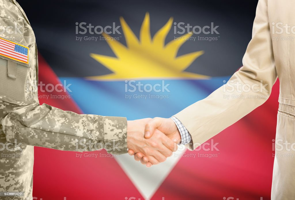 USA military man in uniform and civil man in suit shaking hands with adequate national flag on background - Antigua and Barbuda stock photo