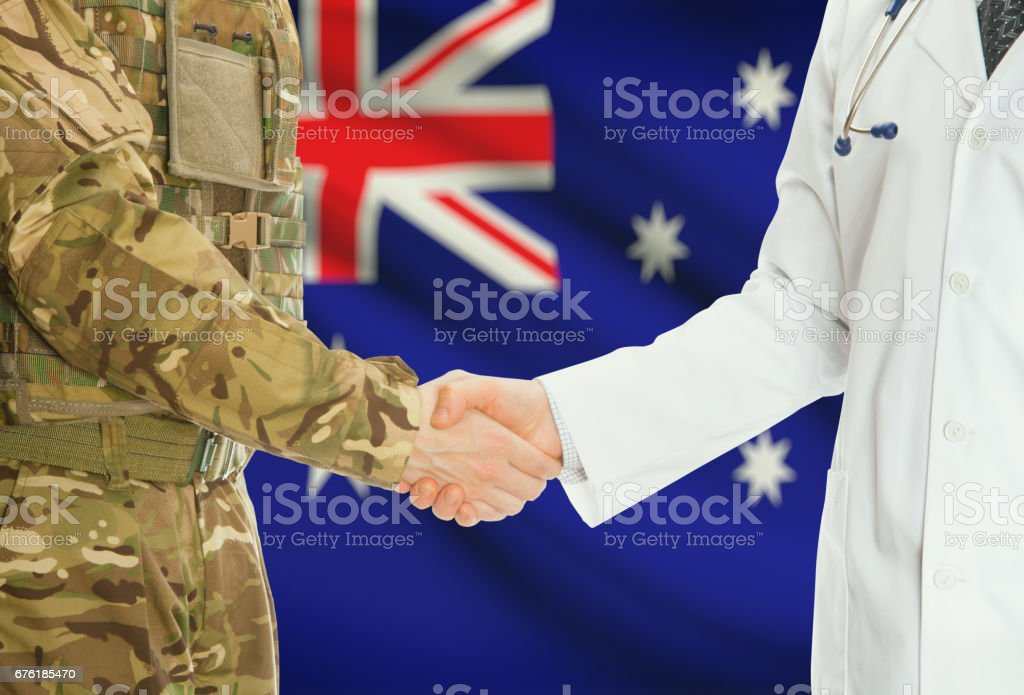 Military man in uniform and doctor shaking hands with national flag on background - Australia stock photo