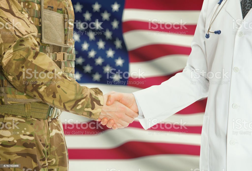 Military man in uniform and doctor shaking hands with national flag on background - United States - foto de acervo