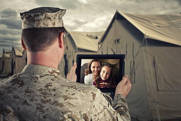militärische mann video-chats mit familie auf einem tablet - camouflagekleidung mädchen stock-fotos und bilder