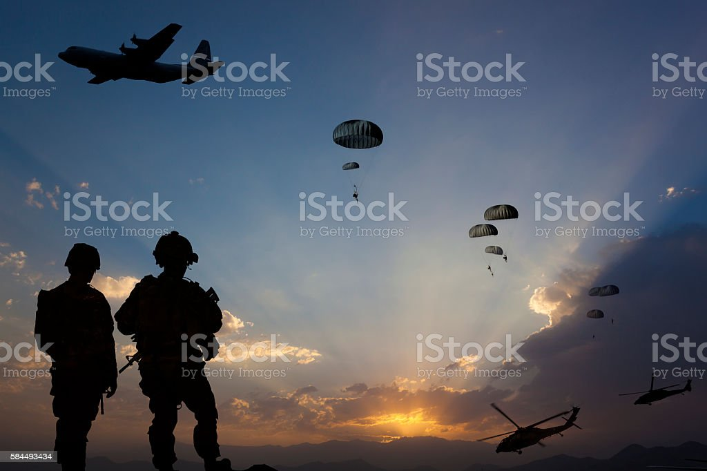 Military Mission at dusk ATTENTION FOR INSPECTOR: This is a composite photo and the date of model releases are different from the date of image. Please consider this. Paratroopers jumping from the plane and military helicopters leave behind soldiers for a night mission. Adult Stock Photo