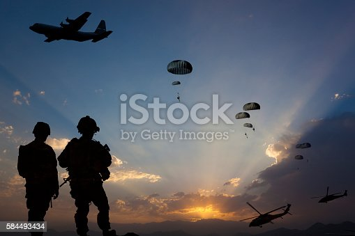 ATTENTION FOR INSPECTOR: This is a composite photo and the date of model releases are different from the date of image. Please consider this. Paratroopers jumping from the plane and military helicopters leave behind soldiers for a night mission.