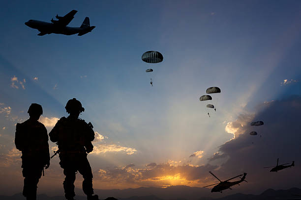 Military Mission at dusk ATTENTION FOR INSPECTOR: This is a composite photo and the date of model releases are different from the date of image. Please consider this. Paratroopers jumping from the plane and military helicopters leave behind soldiers for a night mission. air force stock pictures, royalty-free photos & images