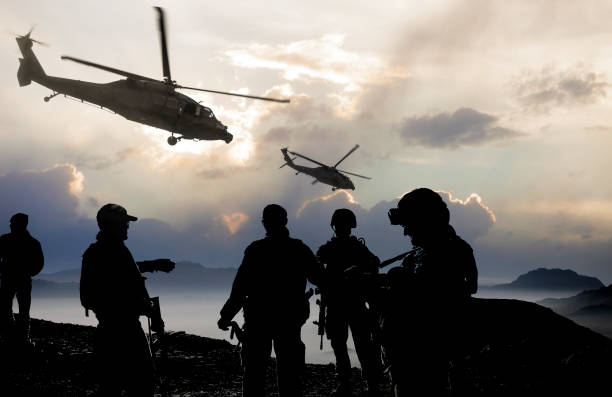 Military Mission at dusk Silhouette of soldiers and helicopters during a military mission at dusk. Afghanistan stock pictures, royalty-free photos & images