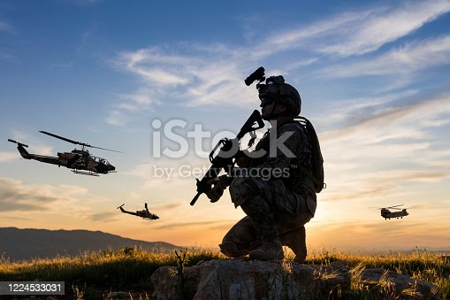 Military Helicopters flying behind kneeling soldier at sunset