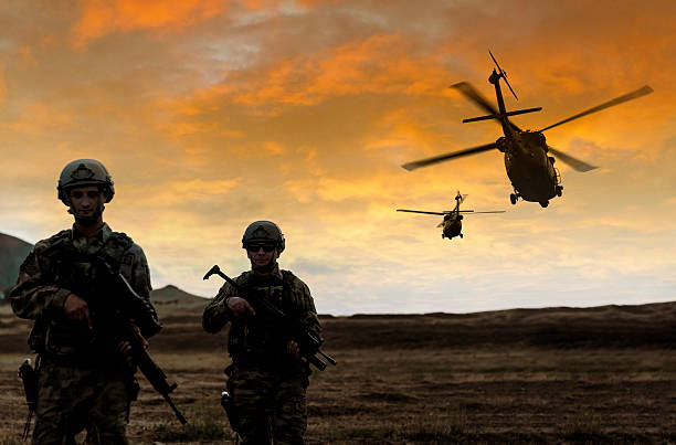 Military Mission on sunset Two soldiers walking in the battlefield while two military helicopter flying over them during a military operation at sunset. battlefield stock pictures, royalty-free photos & images