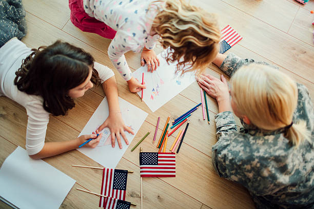 Military Mom Coloring With Her Kids. Military mom lying on floor with her two children, little girls. Coloring and drawing together. Having some happy time together. Mother just return from some of army missions. Top view. Shot with Canon EOS 5Ds 50mp military lifestyle stock pictures, royalty-free photos & images