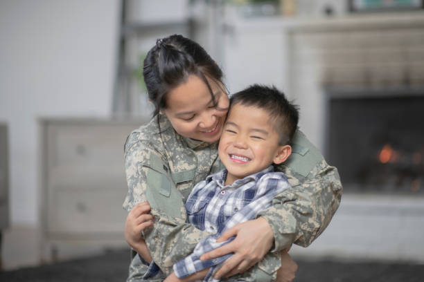 Military Mom Hugging Her Son A mother and her son are hugging in their living room. The mother is wearing a military uniform. military lifestyle stock pictures, royalty-free photos & images